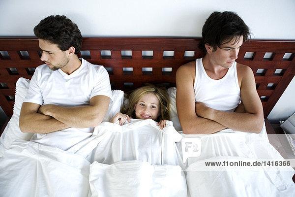 Junge lächelnde Frau im Bett zwischen 2 Männern  Arme gekreuzt