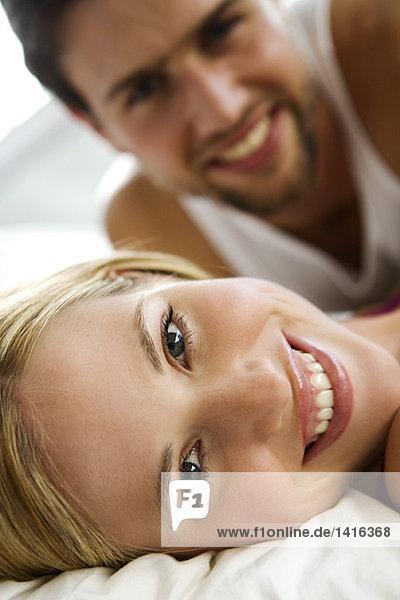 Junges lächelndes Paar im Bett