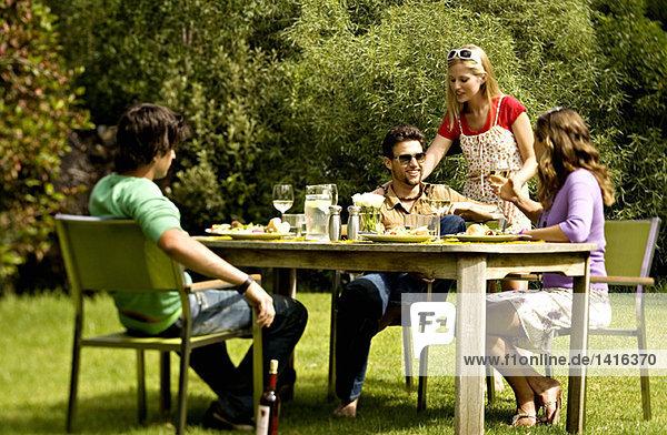 2 junge Paare sitzen am Gartentisch