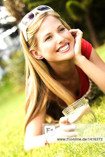 Junge lächelnde Frau auf Gras liegend  Glas Wasser