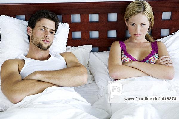 Junges Paar im Bett  Arme gekreuzt