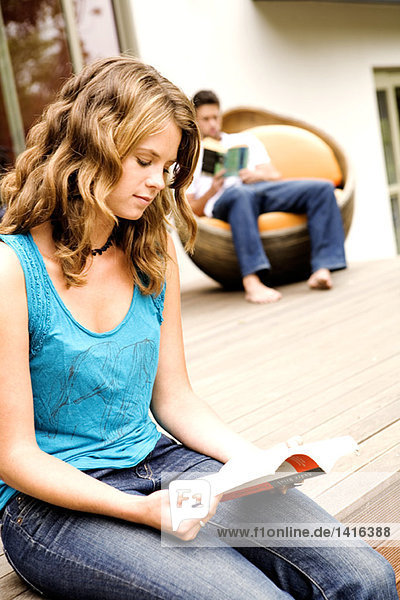Junges Paar beim Lesen im Freien
