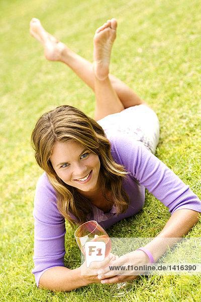 Junge lächelnde Frau auf Gras liegend  Glas Wein