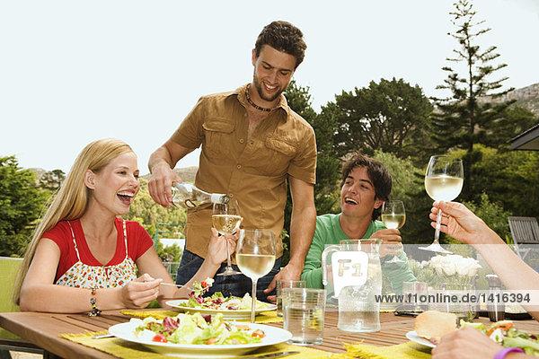2 junge lächelnde Paare sitzen am Gartentisch  Mann schüttet Wein aus