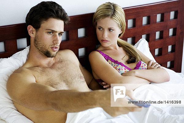 Junges Paar im Bett  fernsehen