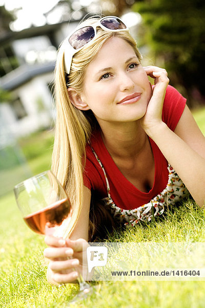 Junge Frau auf Gras liegend  Glas Wein