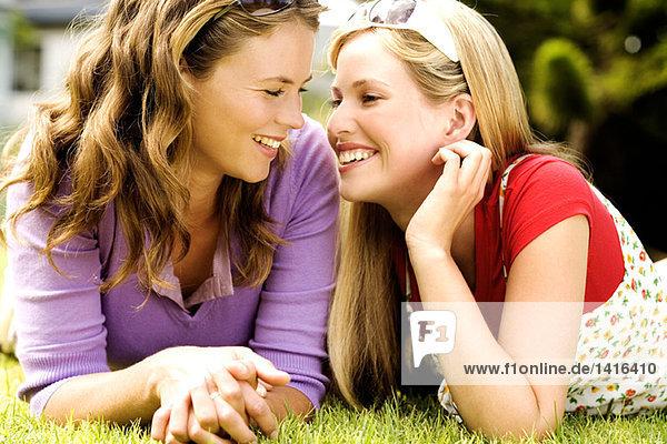 2 junge lächelnde Frauen  die auf Gras liegen und sich anschauen