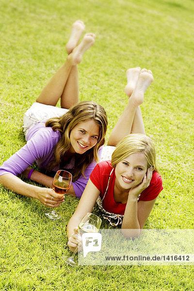 2 junge lächelnde Frauen auf Gras liegend  Gläser Wein