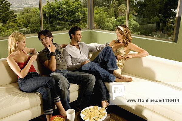 2 junge lächelnde Paare  die auf dem Sofa sitzen und reden