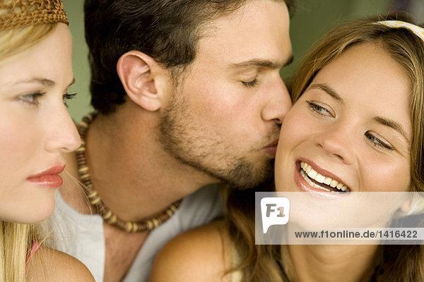Junge Frau schaut den Mann an  der die lächelnde Frau küsst.