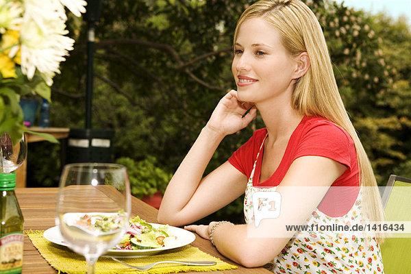 Junge Frau am Gartentisch sitzend