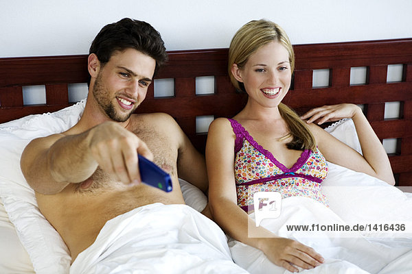 Young smiling couple in bed  watching TV