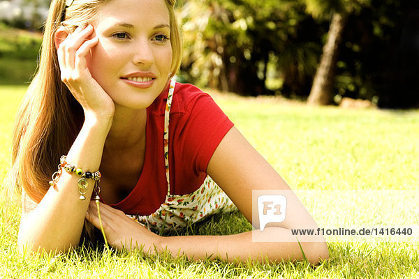Junge Frau auf Gras liegend