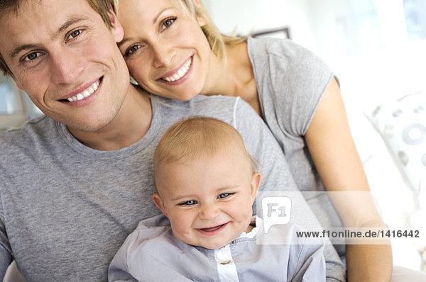 Portrait Eltern und Baby lächelnd  drinnen