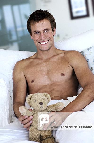 Junger Mann lächelnd  Blick in die Kamera  Teddybär in den Händen  drinnen