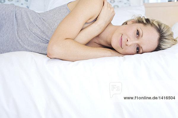 Junge Frau mit Blick in die Kamera  auf dem Bett liegend  drinnen
