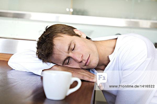 Porträt eines Mannes  der auf dem Tisch in der Küche schläft  drinnen