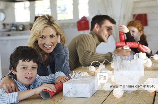 Paarwerbung für drei Kinder  die um den Tisch sitzen  Weihnachtsgeschenke austauschen  drinnen