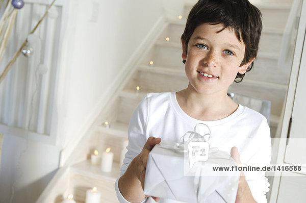 Kleiner Junge mit Weihnachtsgeschenk  drinnen