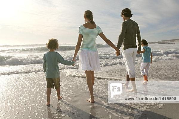 Eltern und zwei Kinder beim Spaziergang am Strand  Rückansicht  im Freien
