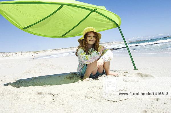 Kleines Mädchen sitzend am Strand unter großem grünen Blatt  draußen