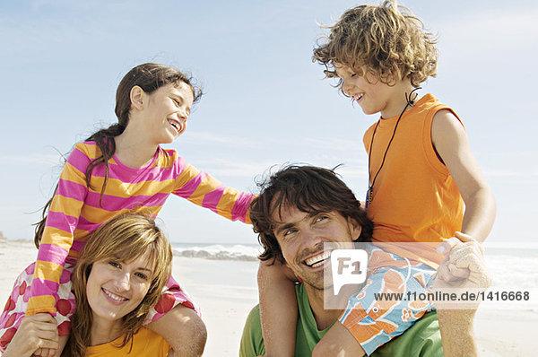 Porträt der Eltern,  die ihre beiden Kinder auf den Schultern,  am Strand und im Freien tragen.