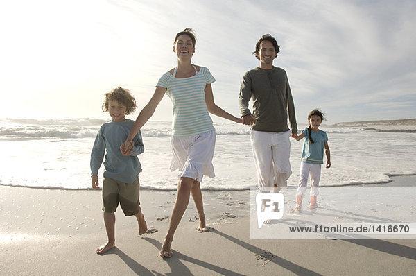 Eltern und zwei Kinder beim Spaziergang am Strand  im Freien