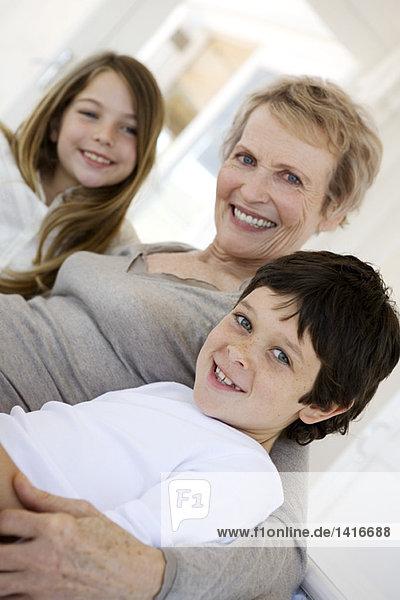 Seniorin und zwei Kinder lächeln für die Kamera  drinnen