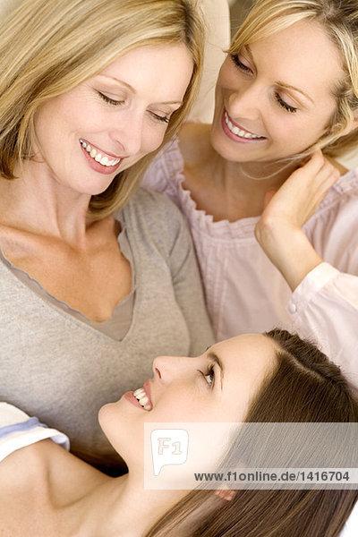Drei lächelnde Frauen schauen sich an  drinnen.