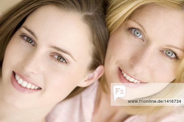 Porträt von zwei Frauen  die für die Kamera lächeln  drinnen