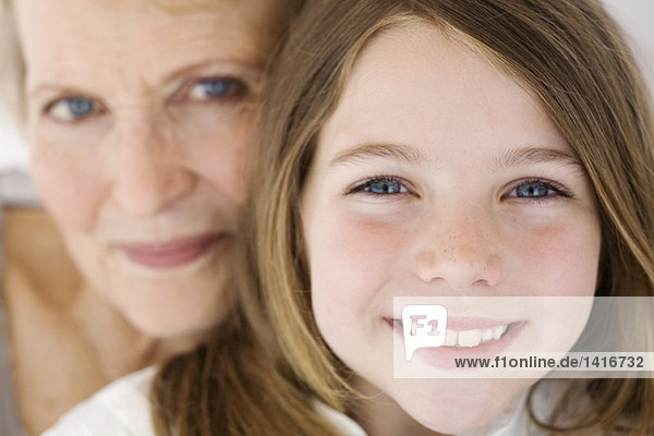 Senior woman and little girl smiling for the camera  indoors