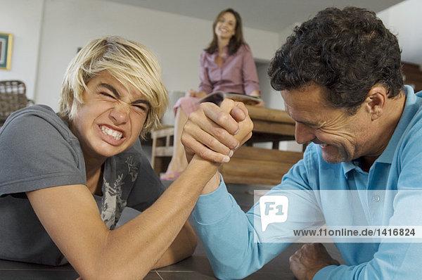 Vater und Sohn Armdrücken im Haus  Mutter im Hintergrund