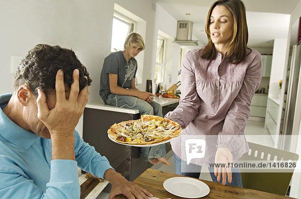 Eltern und Teenager im Wohnzimmer  Frau mit Pizza  drinnen