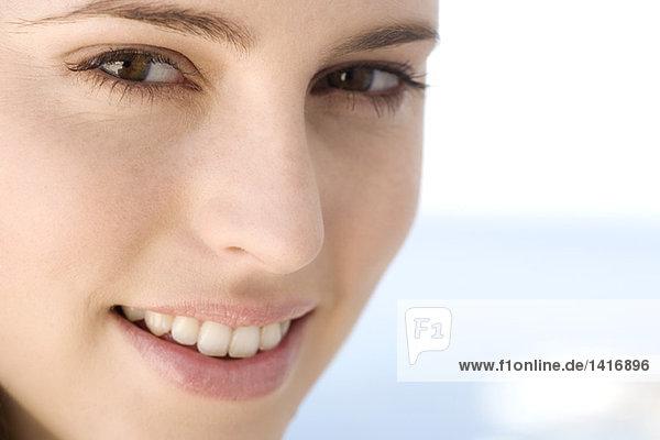Porträt einer lächelnden jungen Frau  die in die Kamera schaut  drinnen