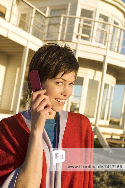Porträt einer jungen Frau mit Handy  im Freien