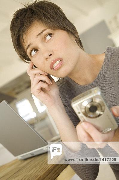 Junge Frau ruft an  hält Digitalkamera in der Hand