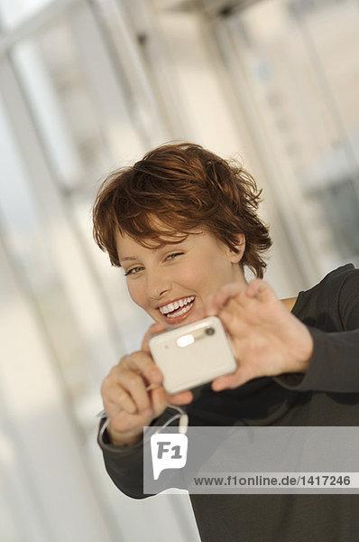 Porträt einer jungen Frau mit Digitalkamera