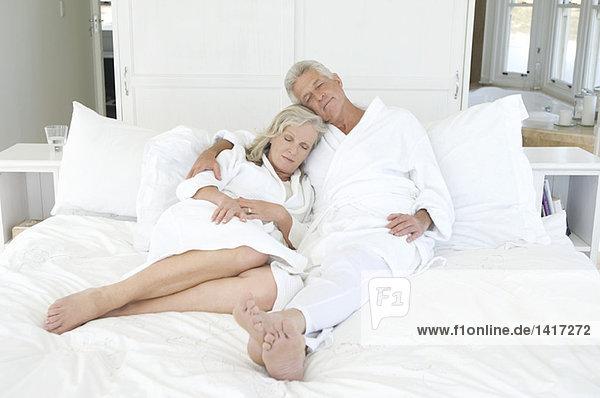 Paar im Bademantel schlafend im Bett