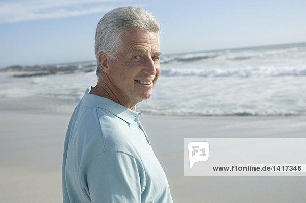 Porträt eines Mannes am Strand  lächelnd für die Kamera