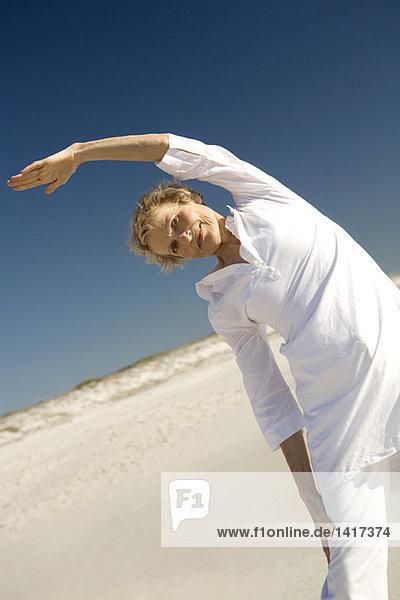 Ältere Frau  die sich am Strand ausstreckt