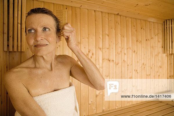 Seniorin kämmt sich in der Sauna die Haare