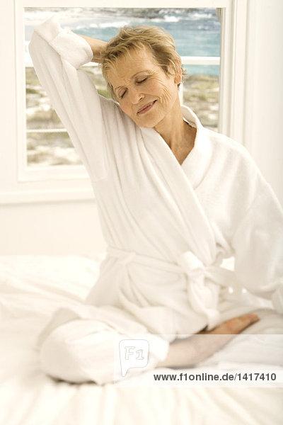 Seniorenfrau im Schneidersitz auf dem Bett