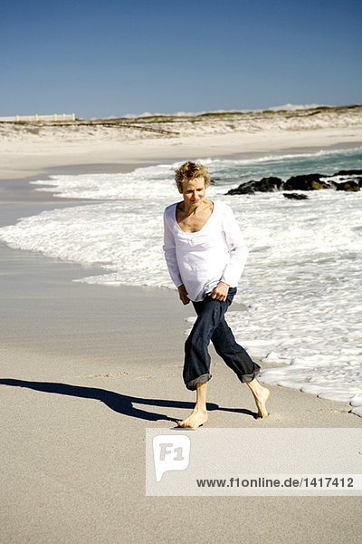 Seniorin beim Spaziergang am Strand
