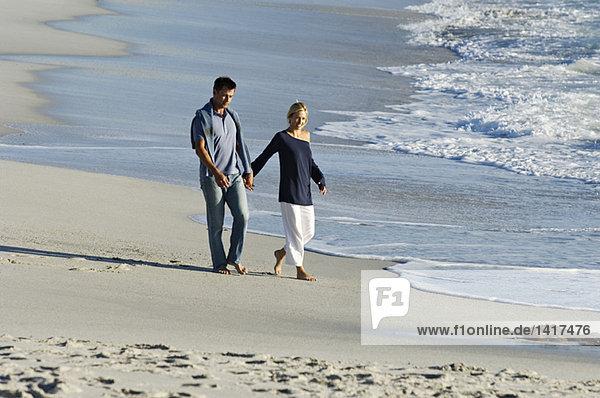 Ein Paar hält sich an den Händen und geht am Strand spazieren.