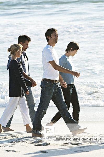 2 Paare halten sich an den Händen und gehen am Strand spazieren.