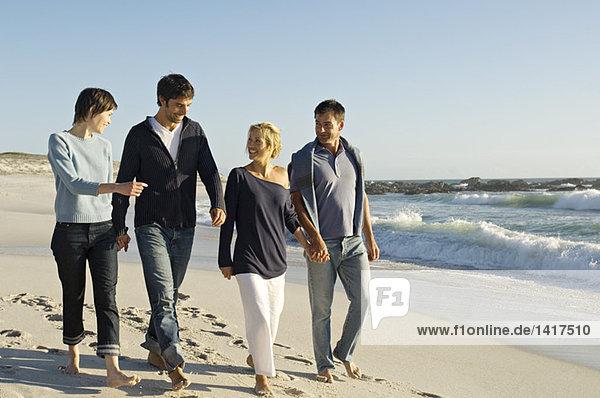 2 Paare  die am Strand spazieren gehen