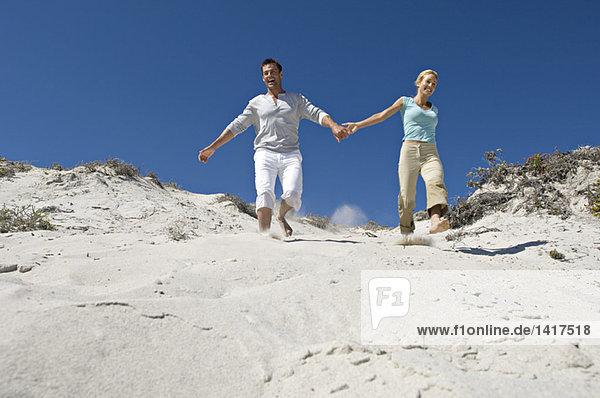 Ein Paar hält sich an den Händen und läuft die Sanddüne hinunter.