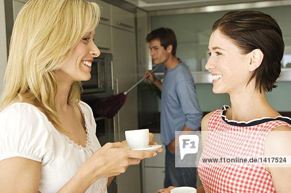 2 lächelnde Frauen im Gespräch  Mann mit Staubwedel im Hintergrund