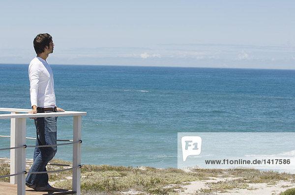 Junger Mann an der Balustrade lehnend  mit Blick aufs Meer