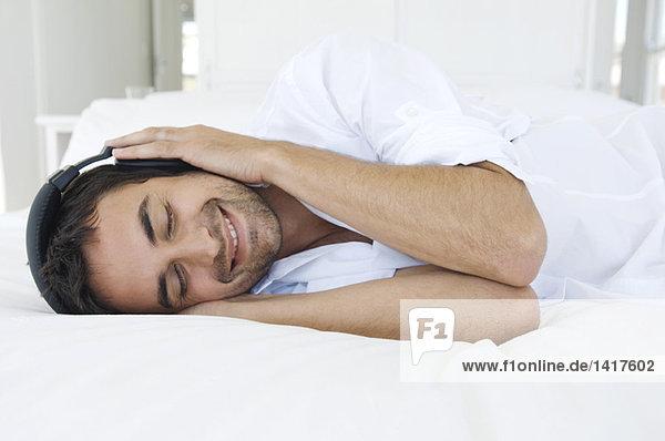 Junger Mann  der mit Kopfhörern Musik hört  auf dem Bett liegend